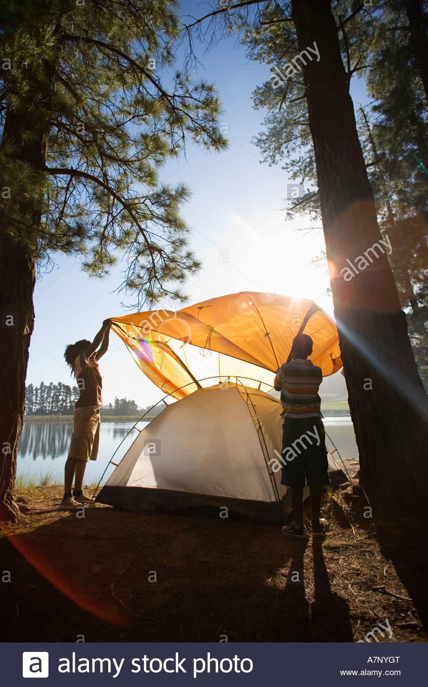 Vater und Sohn 8 10 Montage orange Zelt am See camping Reise Blendenfleck Stockbild