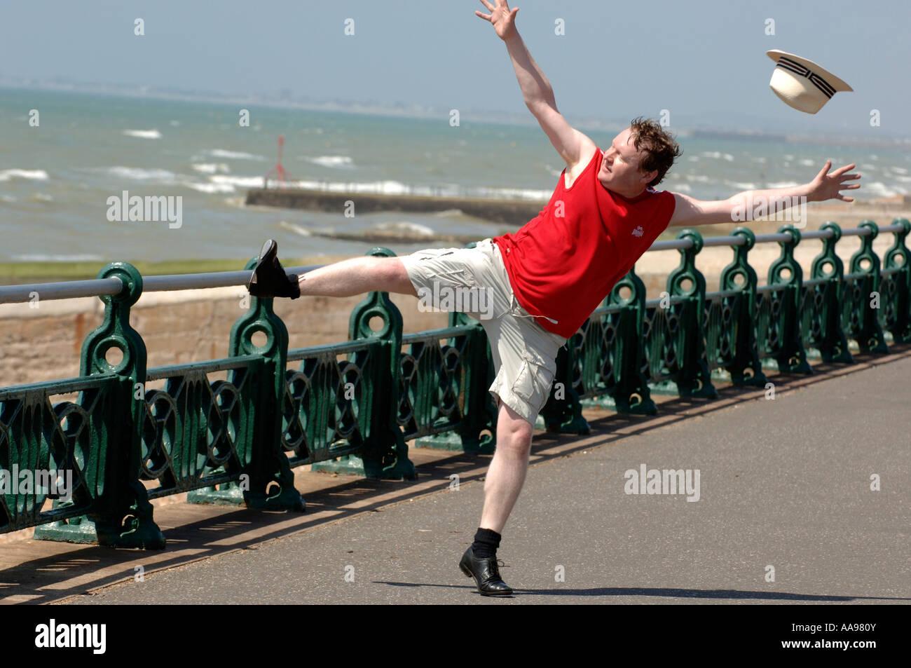 Ein übergewichtiger Mann mittleren Alters dabei ungeschickt hoch treten Tanzprogramm auf Brighton Seafront, Stockbild