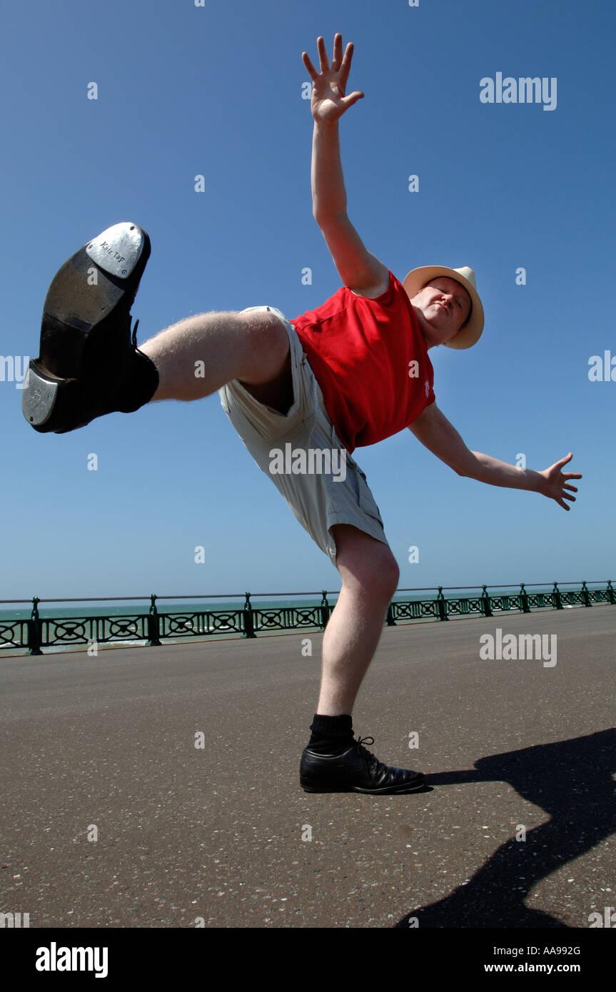 Eine ernsthafte Suche mittleren Alter Mann dabei ungeschickt hohen munter Tanz-Routine auf Brighton seafront Stockbild