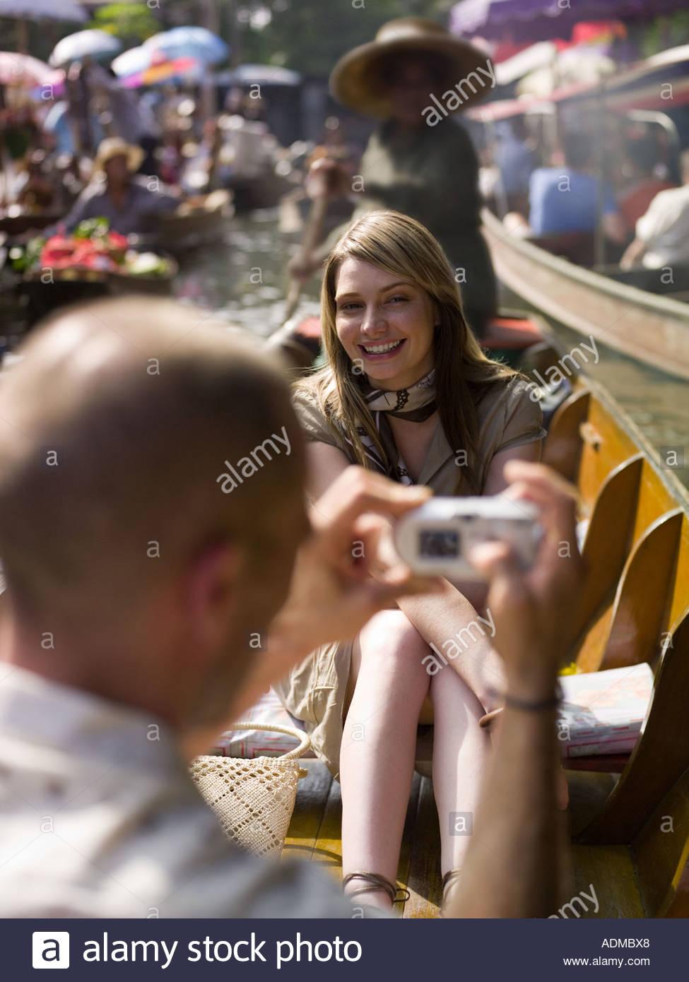 Mann unter Bild der Freundin im Ruderboot Stockbild