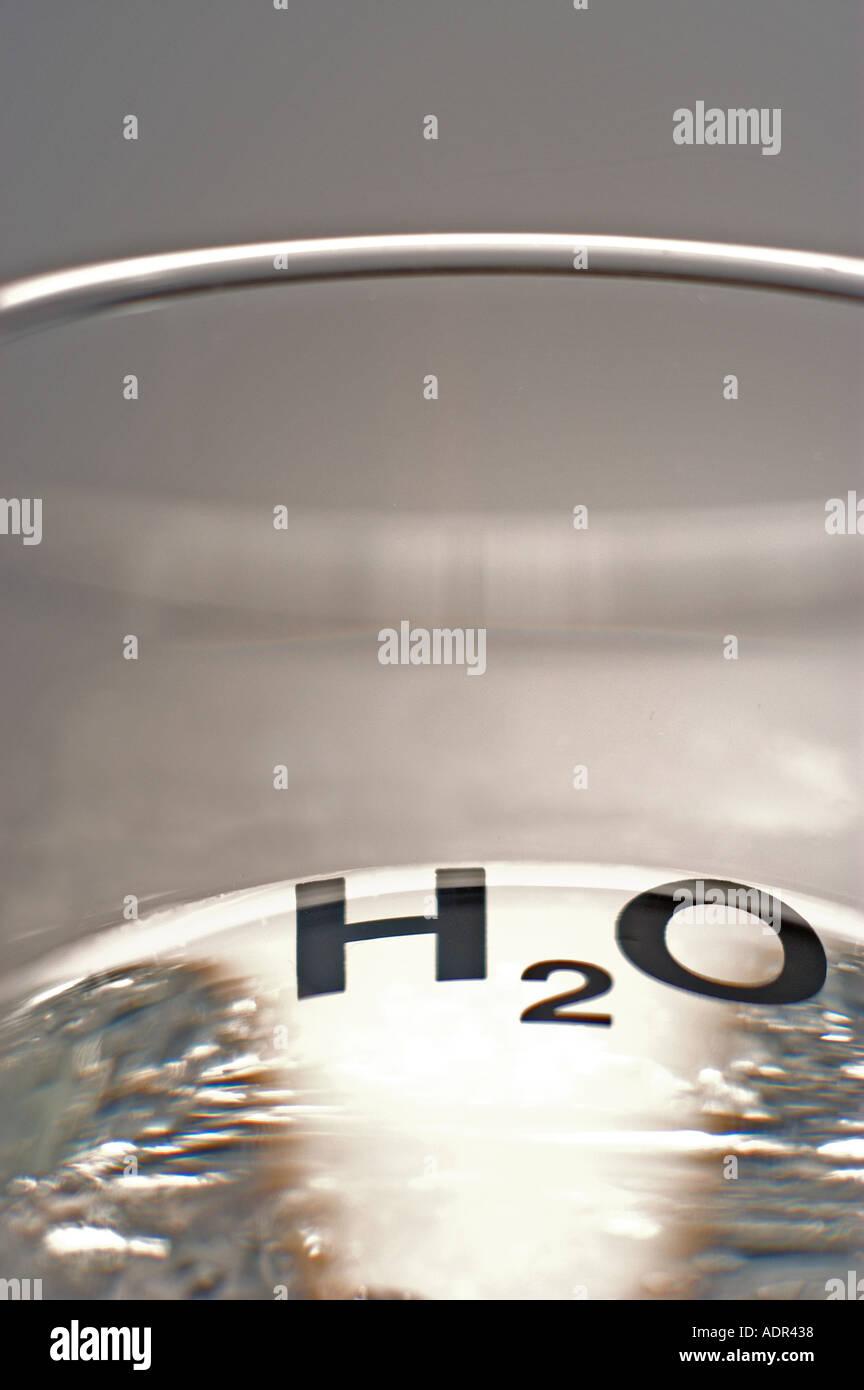 ein Foto von einem Glas Wasser mit H2O Design. Stockbild