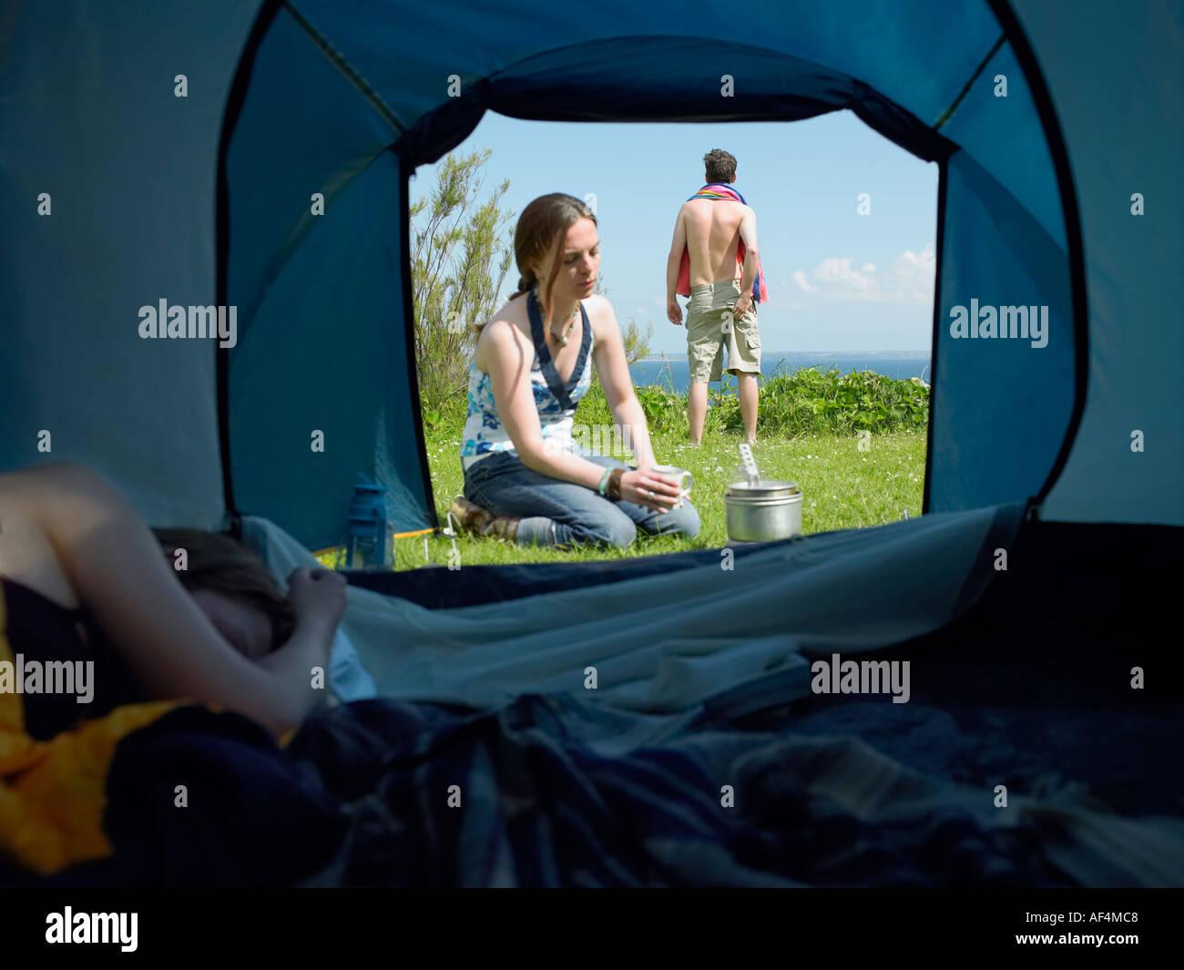 Blick durch Zelt öffnen mit jungen Frauen schlafen innen, während ein anderes mit einem jungen männlichen Stockbild
