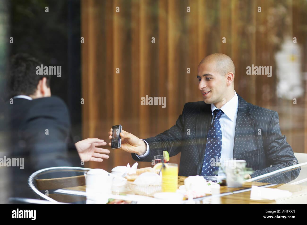 Zwei Geschäftsleute in ein Restaurant mit Blick auf ein Handy Stockbild