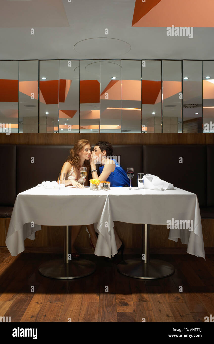 Zwei Frauen in einem Restaurant Flüstern Stockbild