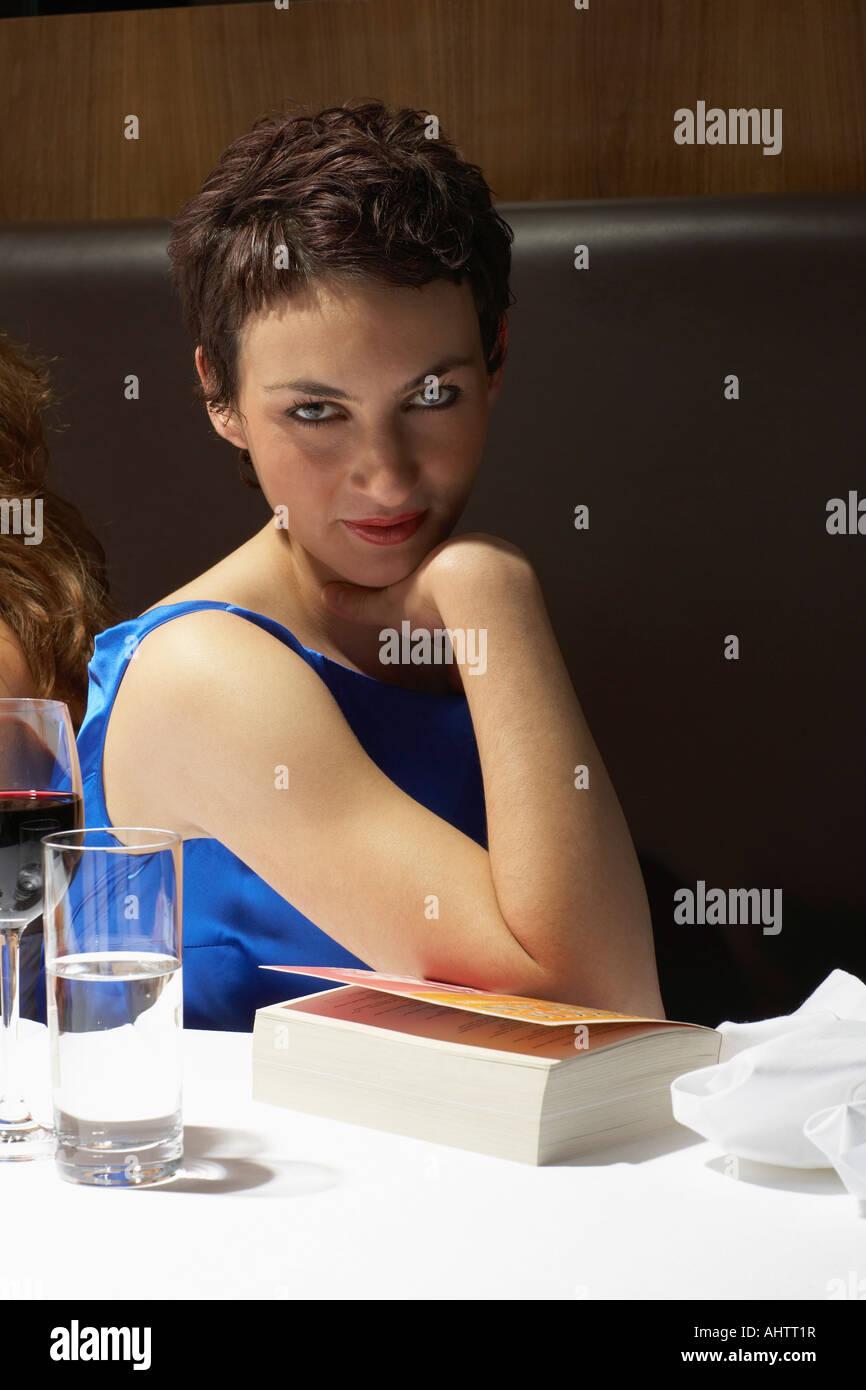 Frau flirtet mit der Kamera in einem Restaurant mit einem Buch Stockbild