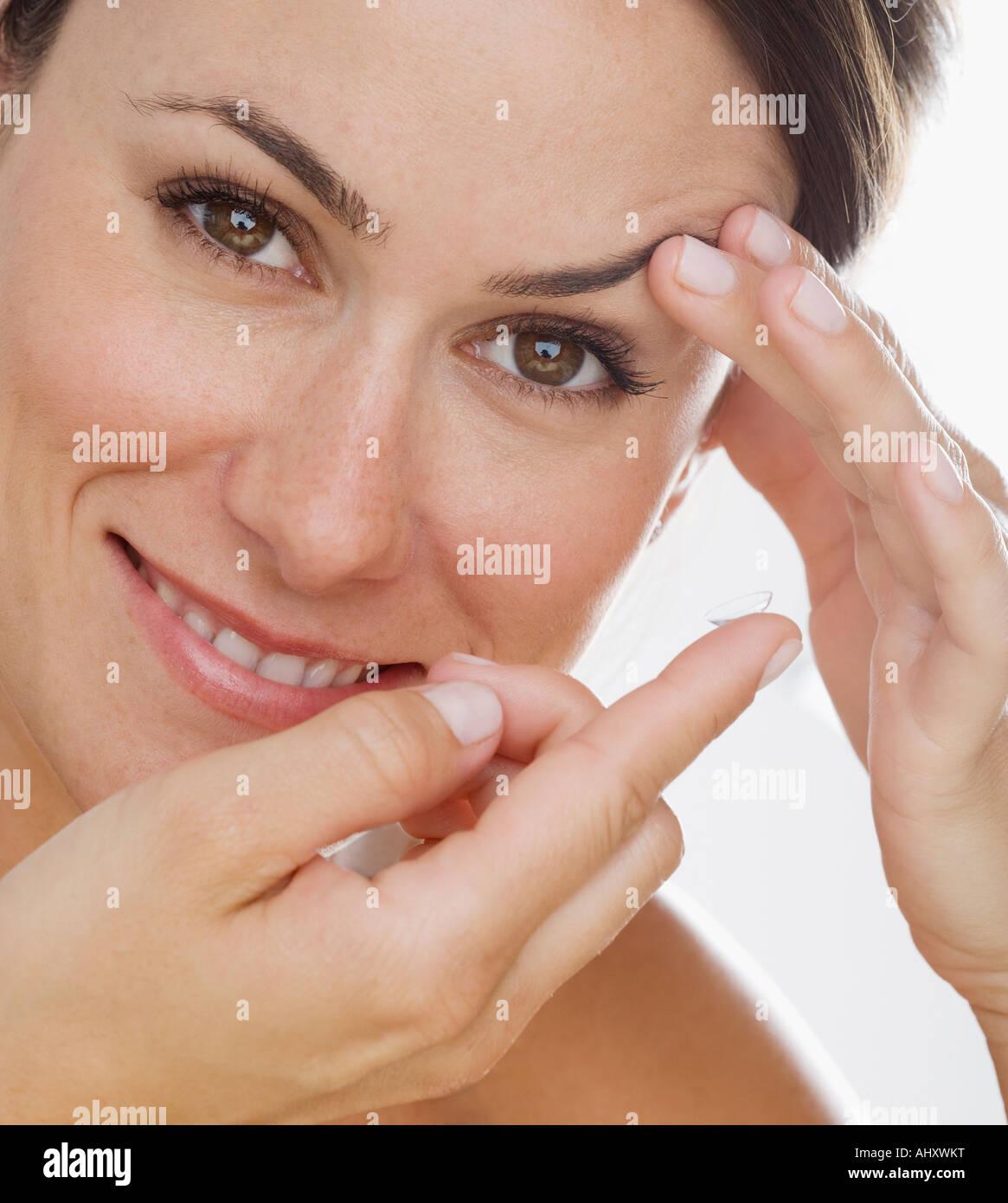Frau in Kontaktlinsen setzen Stockbild
