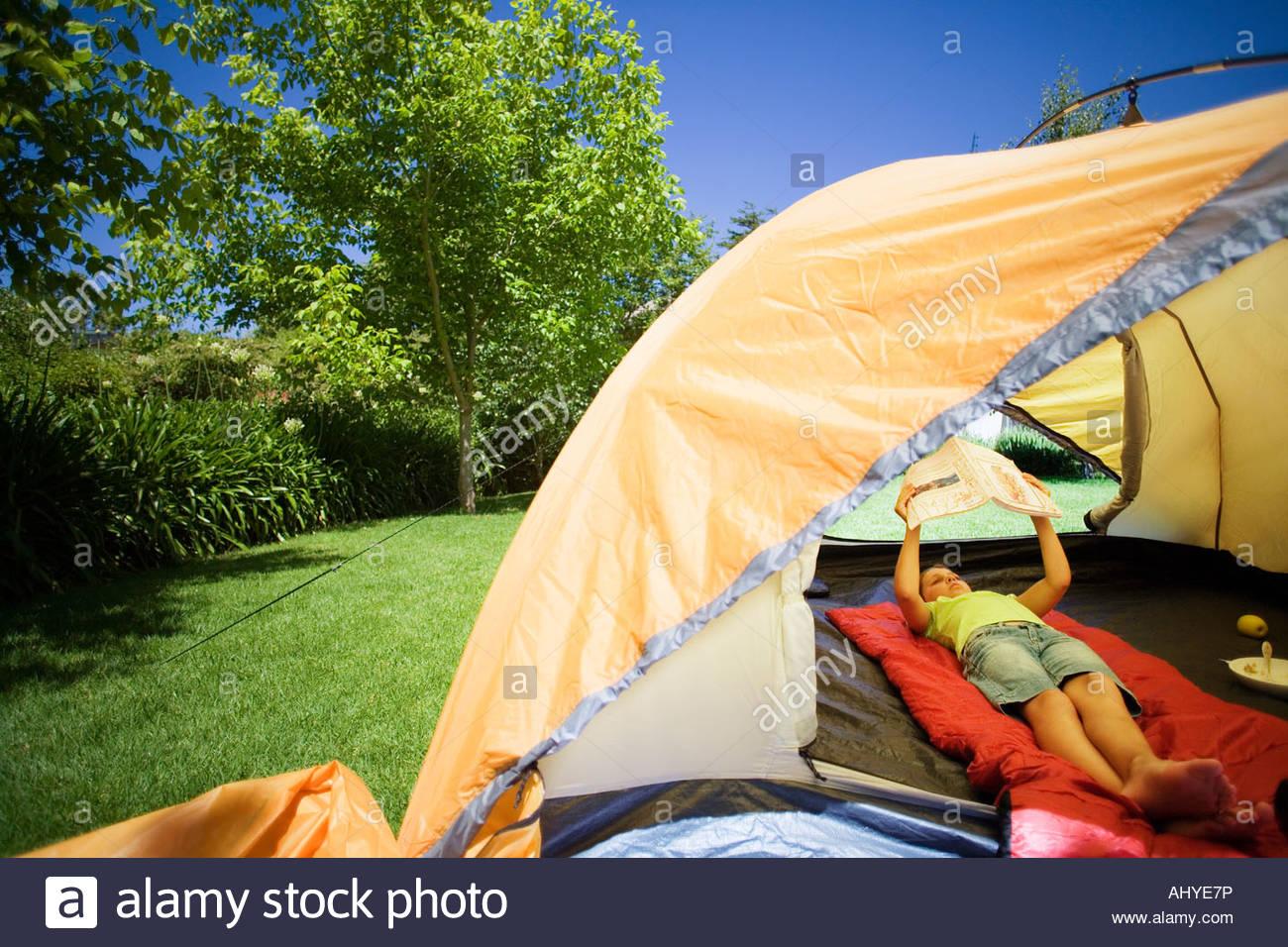 Mädchen 8-10 liegen auf roten Schlafsack in orange Zelt auf der Wiese im Garten Buch Stockbild