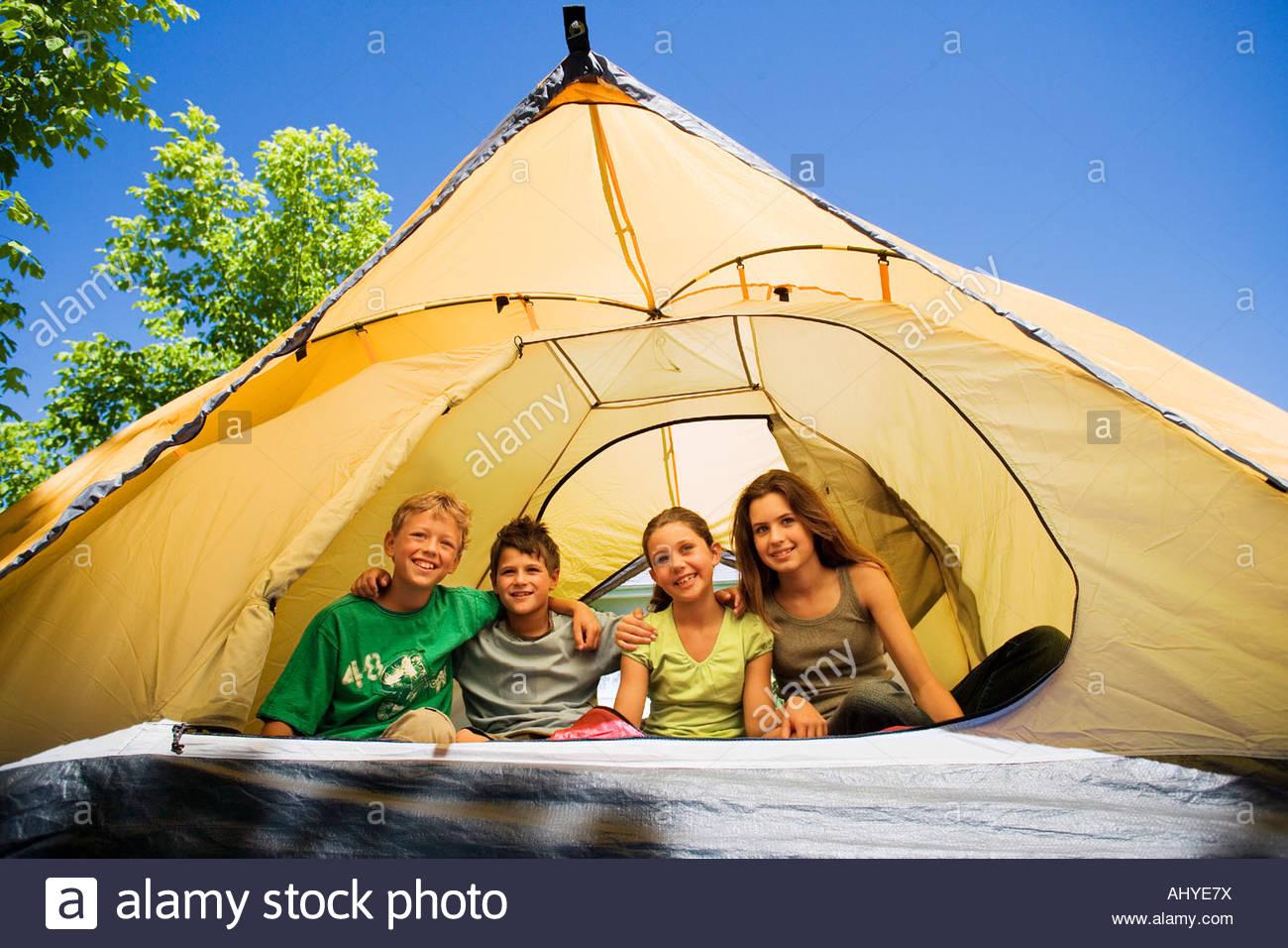 Vier Kinder 8-10 sitzen nebeneinander im Zelt auf der Wiese im Garten lächelnd Vorderansicht Porträt Stockbild
