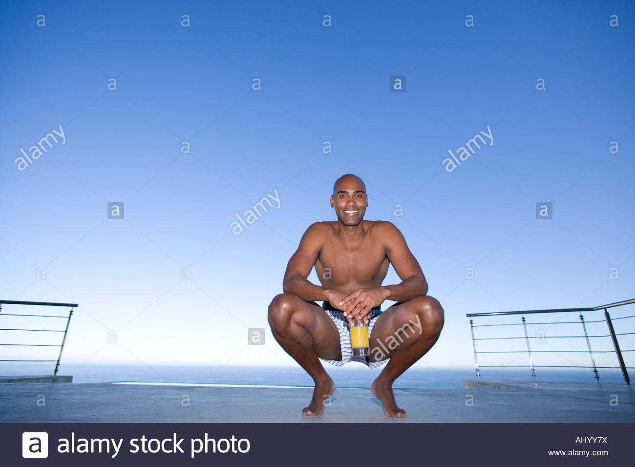 Junger Mann kauert am Boden durch Meer, Lächeln, Porträt Stockbild
