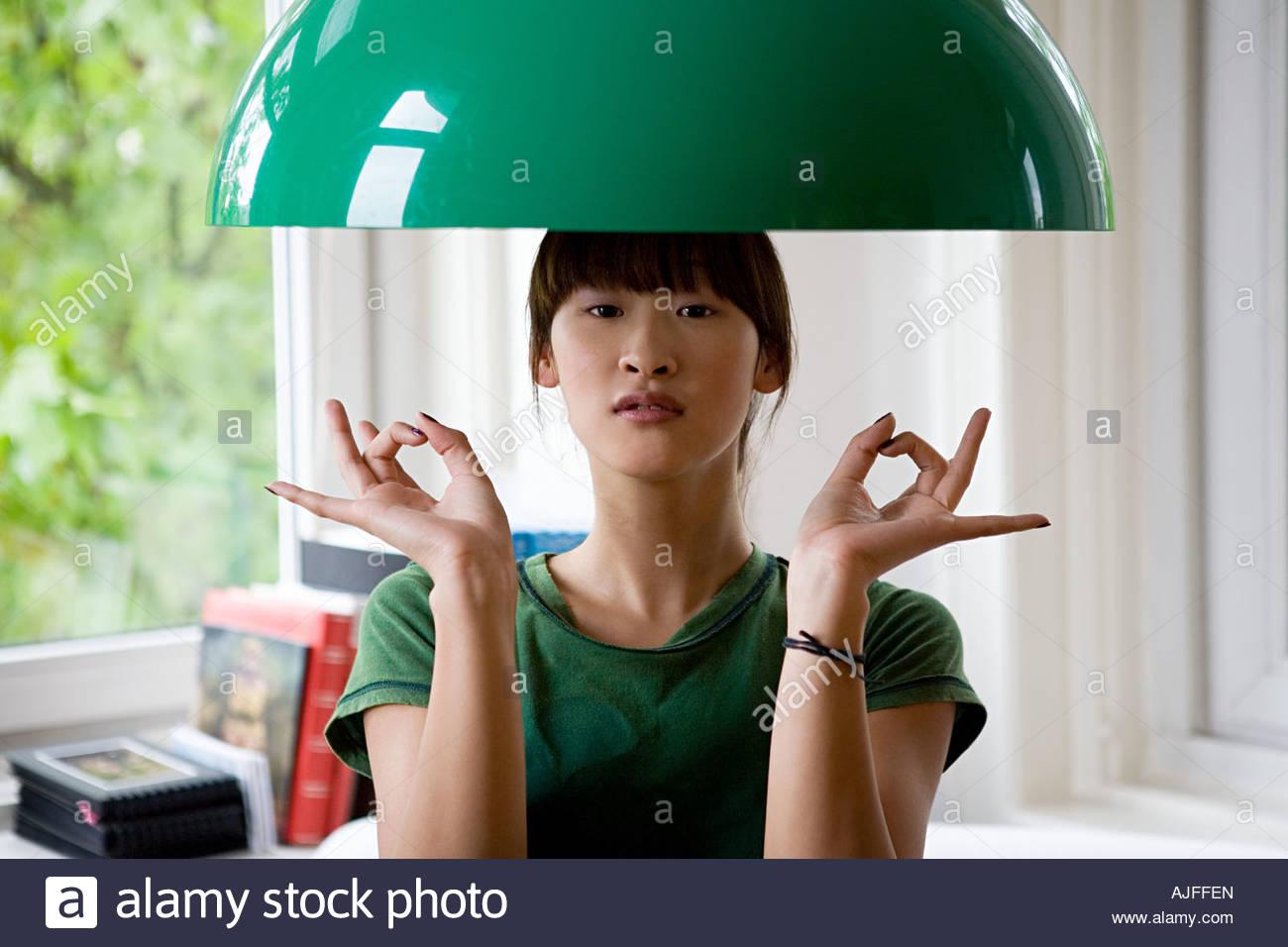 Frau unter Lampenschirm Stockbild