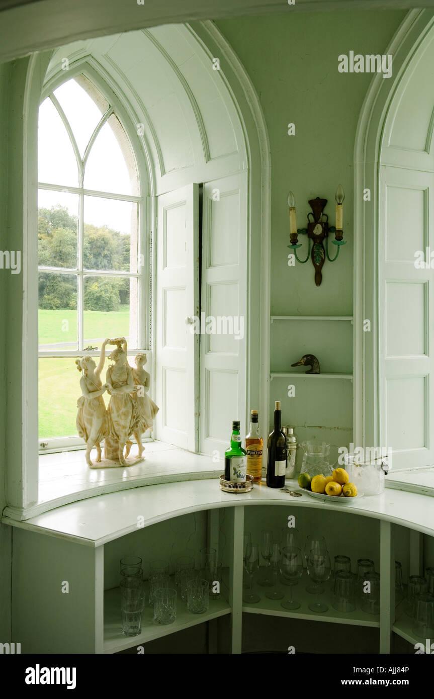 Eingelassene gotisches Fenster mit Fensterläden und Glas Regal mit Getränkeflaschen Stockbild