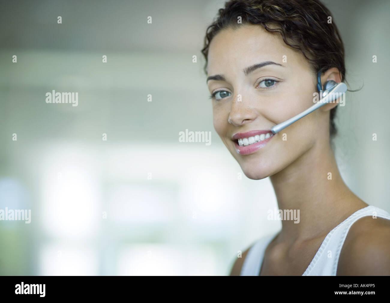 Frau trägt Kopfhörer und lächelnd Stockbild