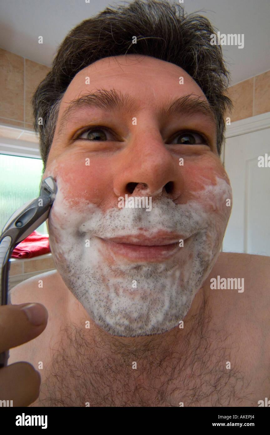 Mann Ende dreißig 30 die Nassrasur mit Seifenschaum auf Gesicht zu rasieren, rasieren Stockbild