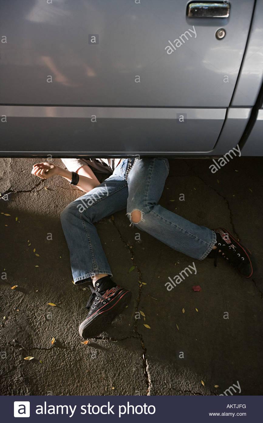 Ein Junge, der unter einem Auto versteckt Stockbild