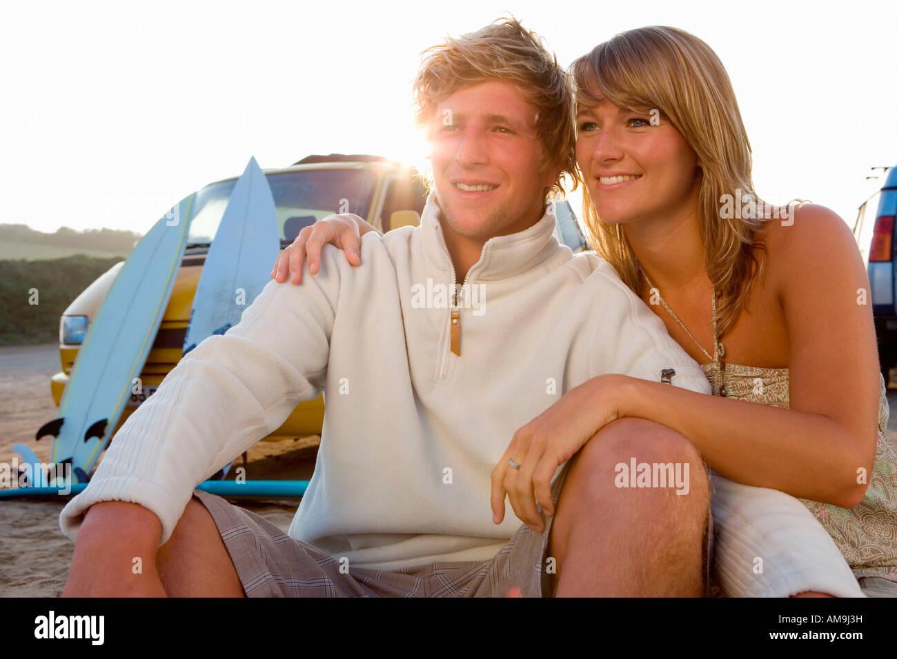 Paar am Strand lächelnd mit van und Surfbretter im Hintergrund sitzt. Stockbild