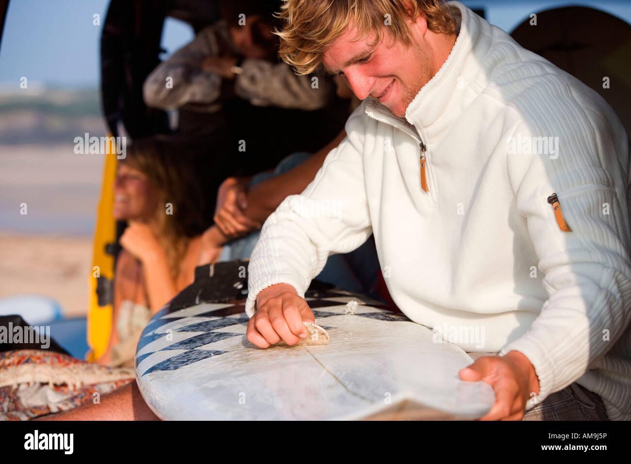 Der Mensch wachsen Surfbrett mit paar lächelnd im Hintergrund. Stockbild