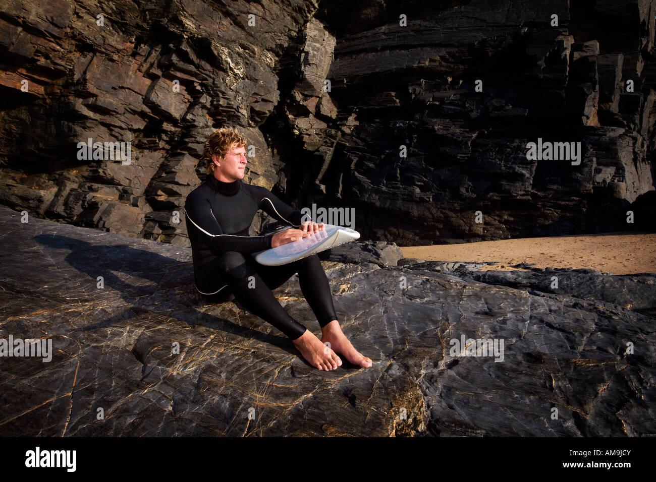 Mann, sitzend auf große Felsen im Neoprenanzug mit Surfbrett auf Schoß. Stockbild
