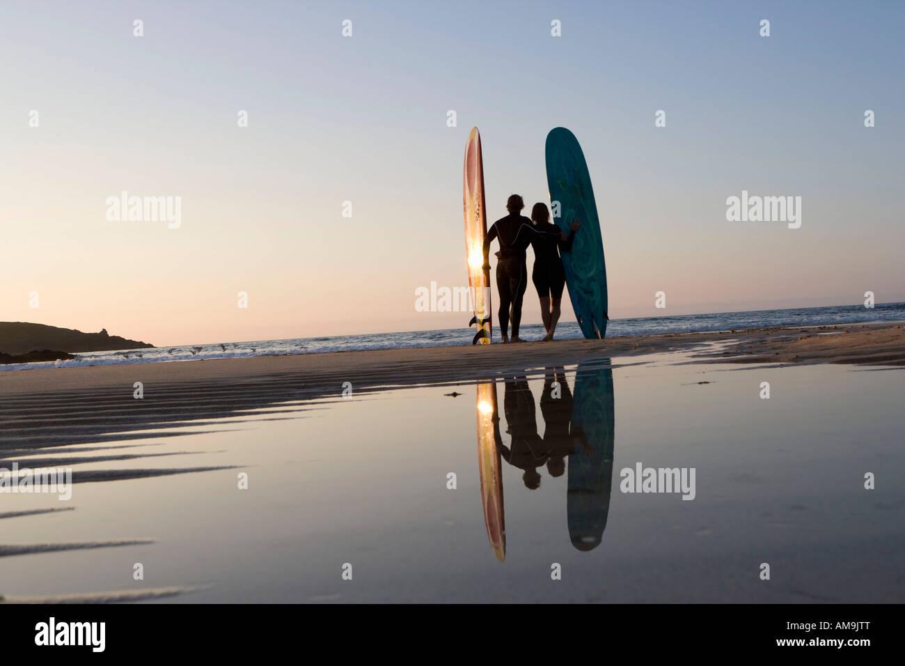 Paar steht am Strand mit Surfbrettern. Stockbild