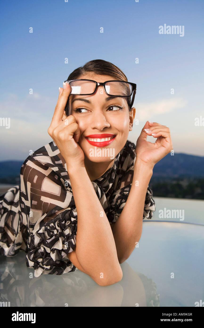 Frau Brillen auf Kopf lächelnd im Freien treibt. Stockbild