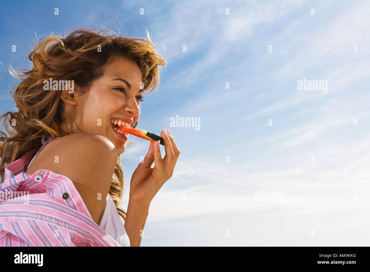 Frau mit Lächeln isst Wassermelone außerhalb. Stockbild