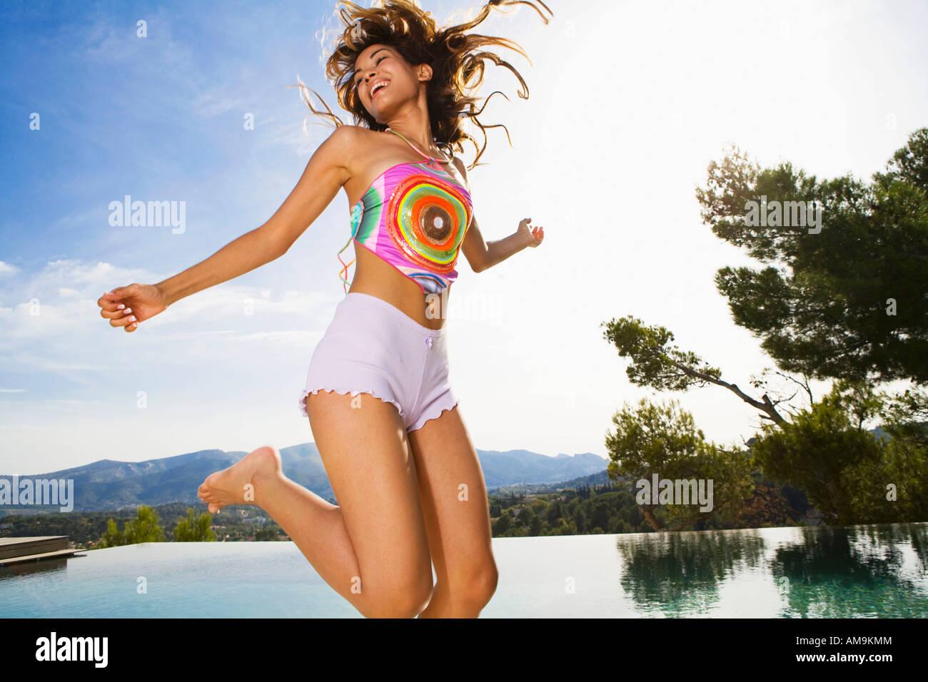 Frau in der Nähe einer Inifinity Pool lächelnd springen. Stockbild