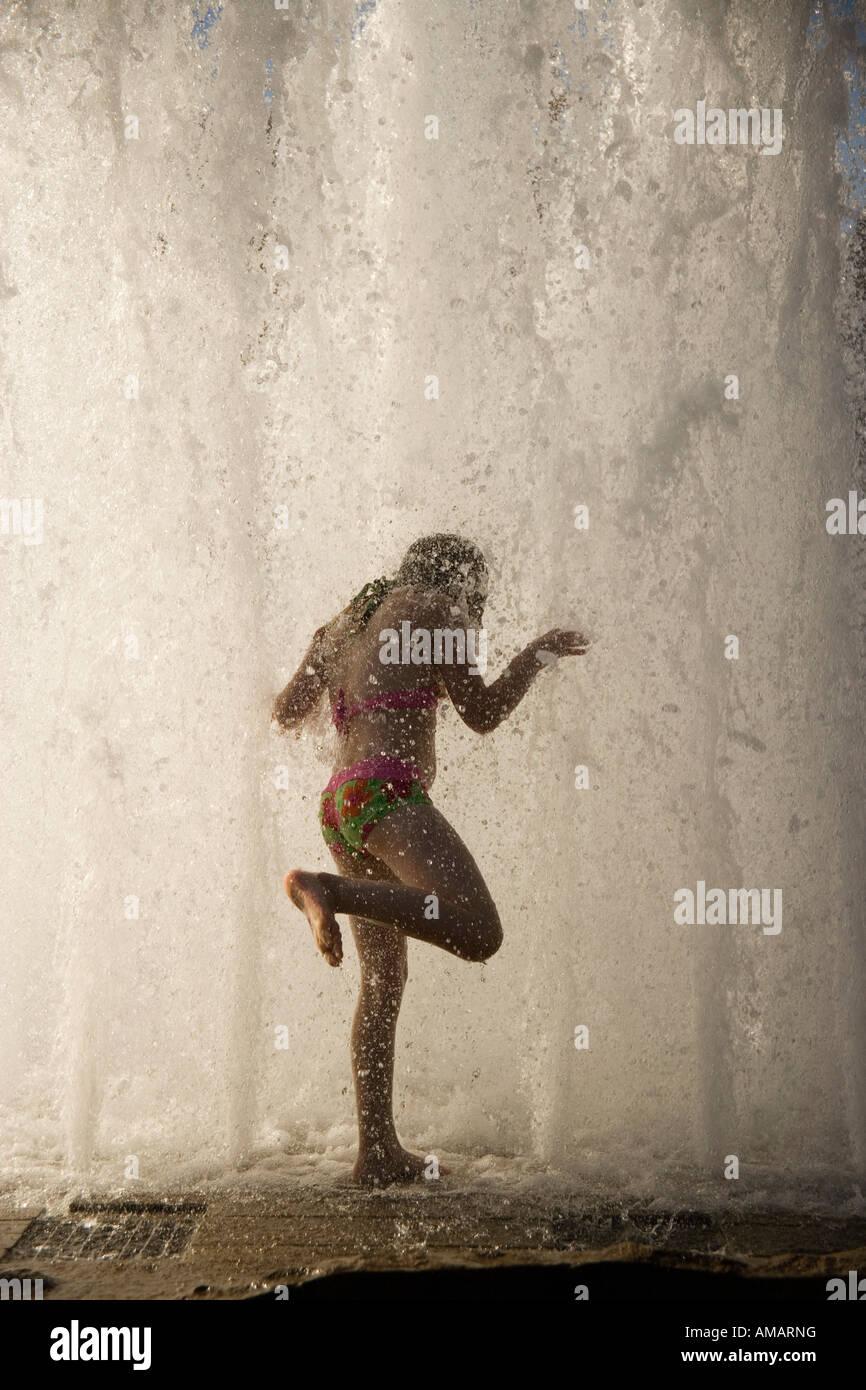 Eine Frau stand unter einem Wasserfall Stockbild