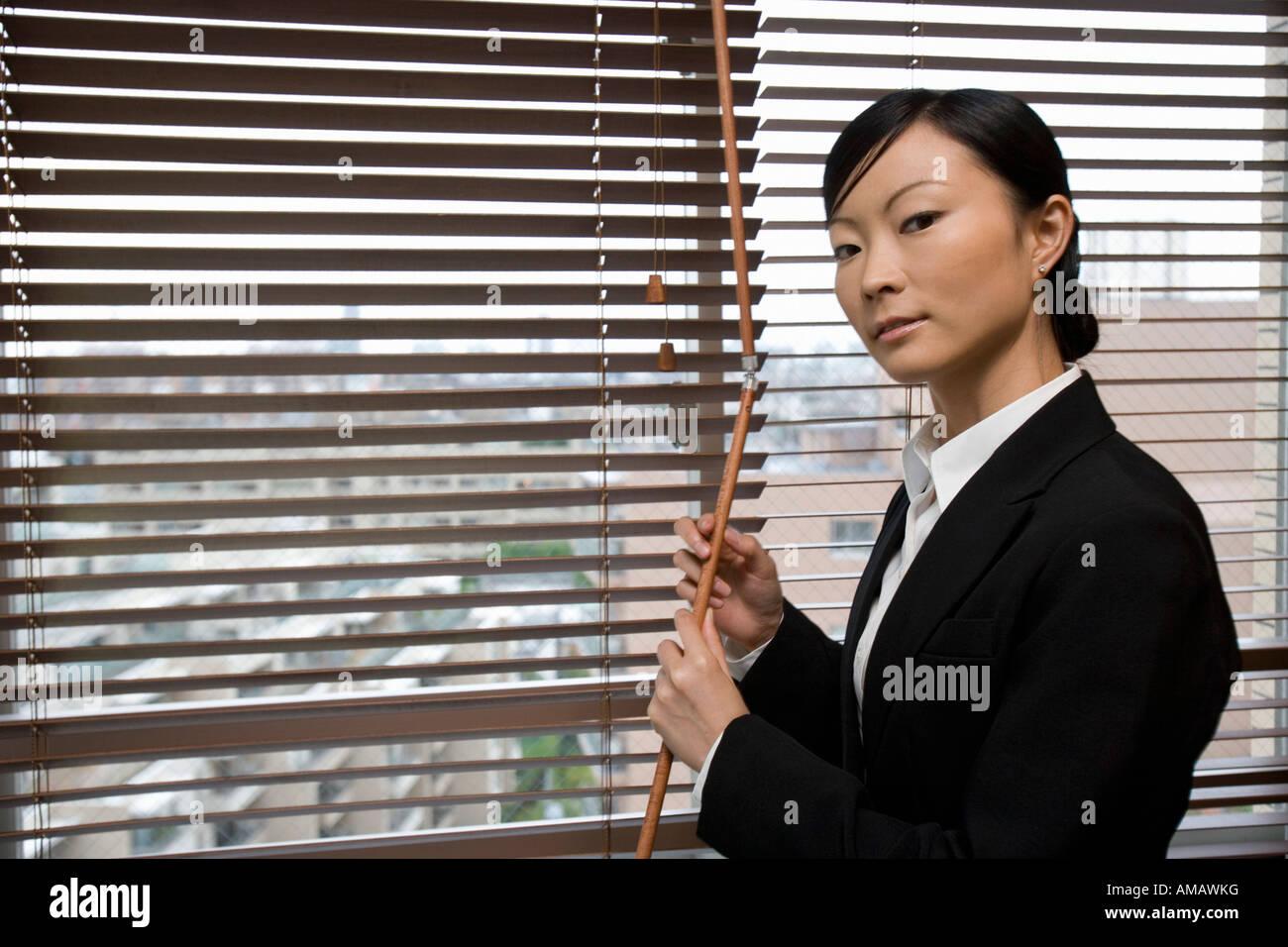 Eine Geschäftsfrau öffnenden Fenster Jalousien Stockbild