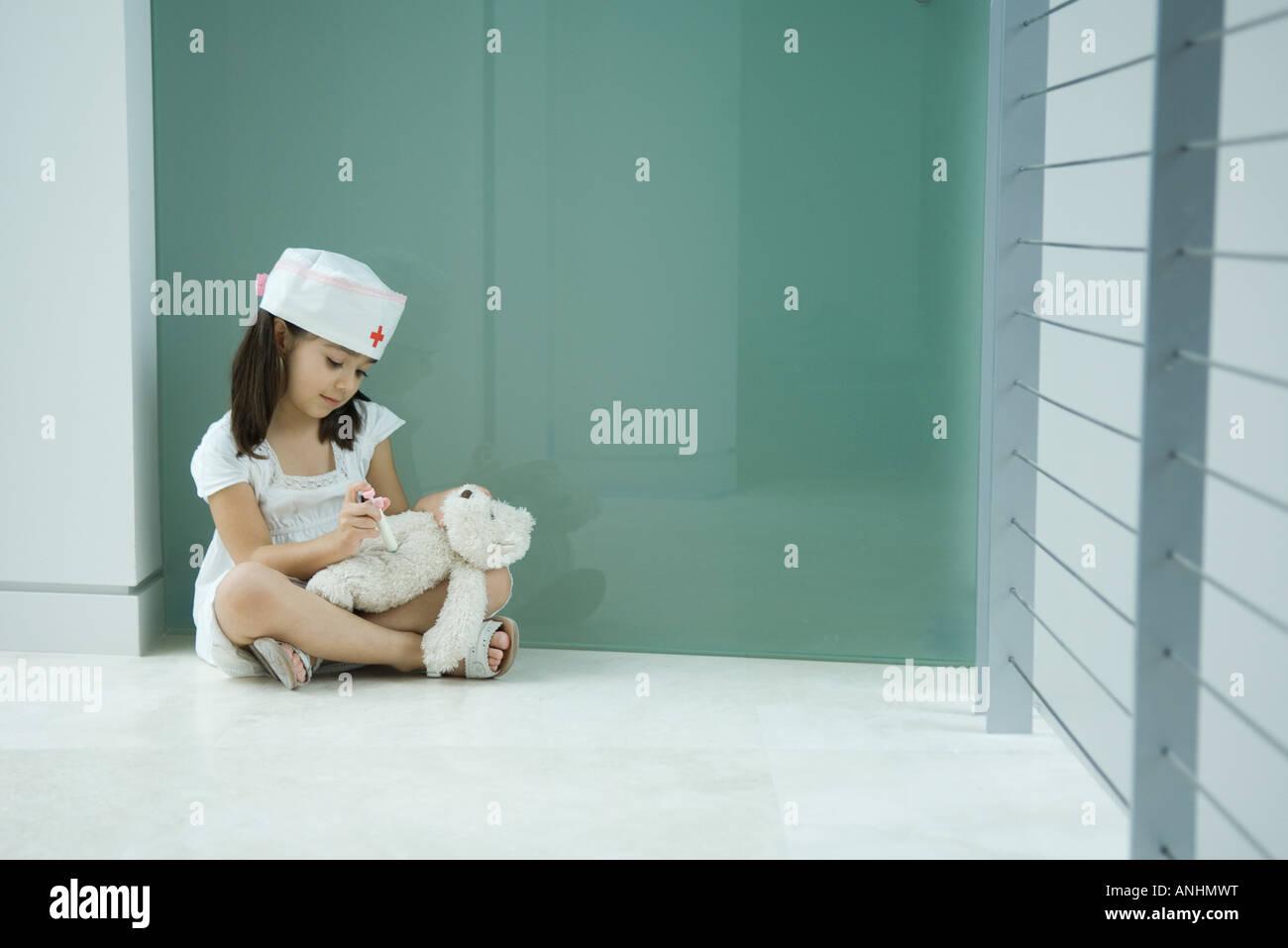 Kleines Mädchen in Krankenschwester Hut geben Teddy Bär erschossen Stockbild