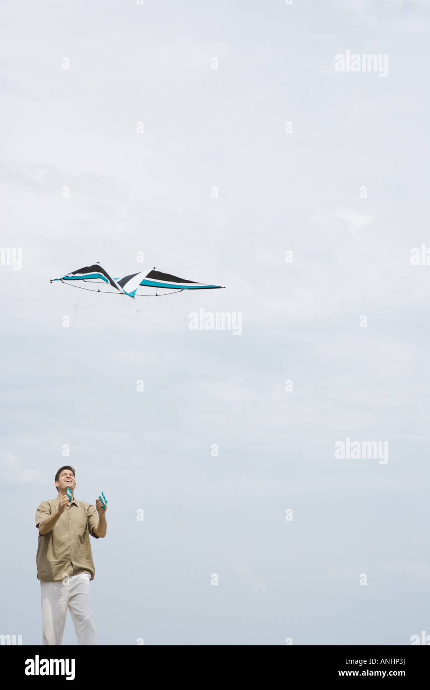 Mann, fliegende Drachen, nachschlagen, drei Viertel Länge Stockbild