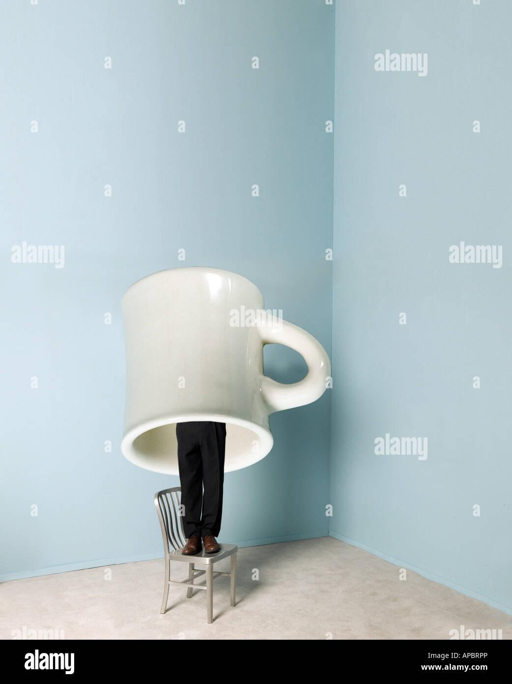 Business-Mann steht oder versteckt unter riesigen Kaffee Tasse Humor lustig Stockbild