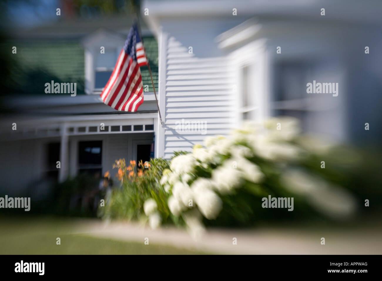 Undeutliches Bild des weißen Schindeln Haus Maine USA Neuengland mit amerikanischen Flagge und Hortensie Blumen Stockbild
