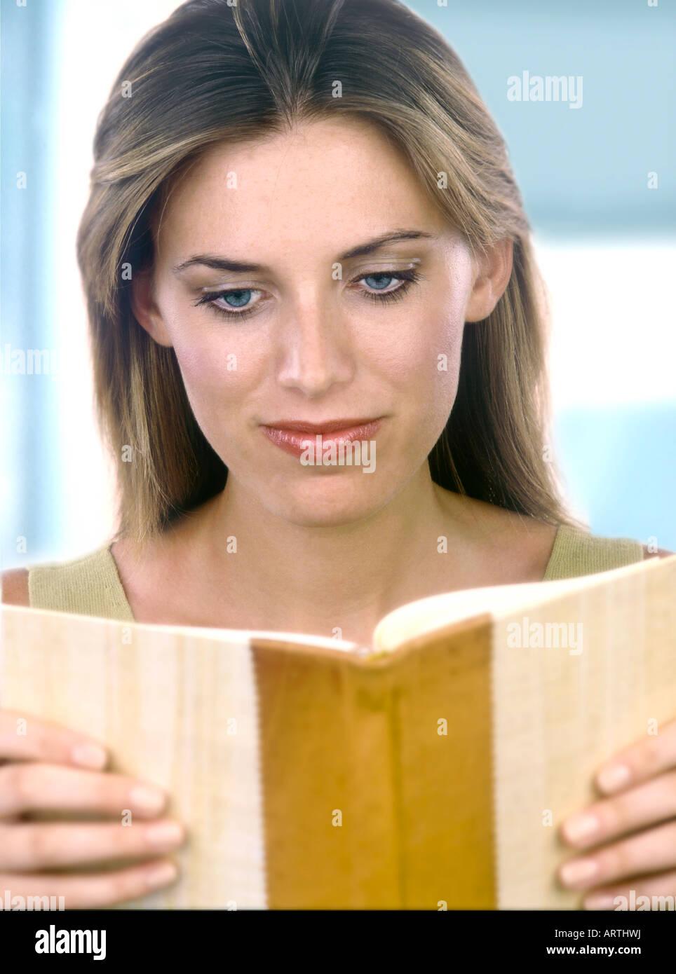 Eine Frau liest ihre Gedanken in ihrem Tagebuch Stockbild