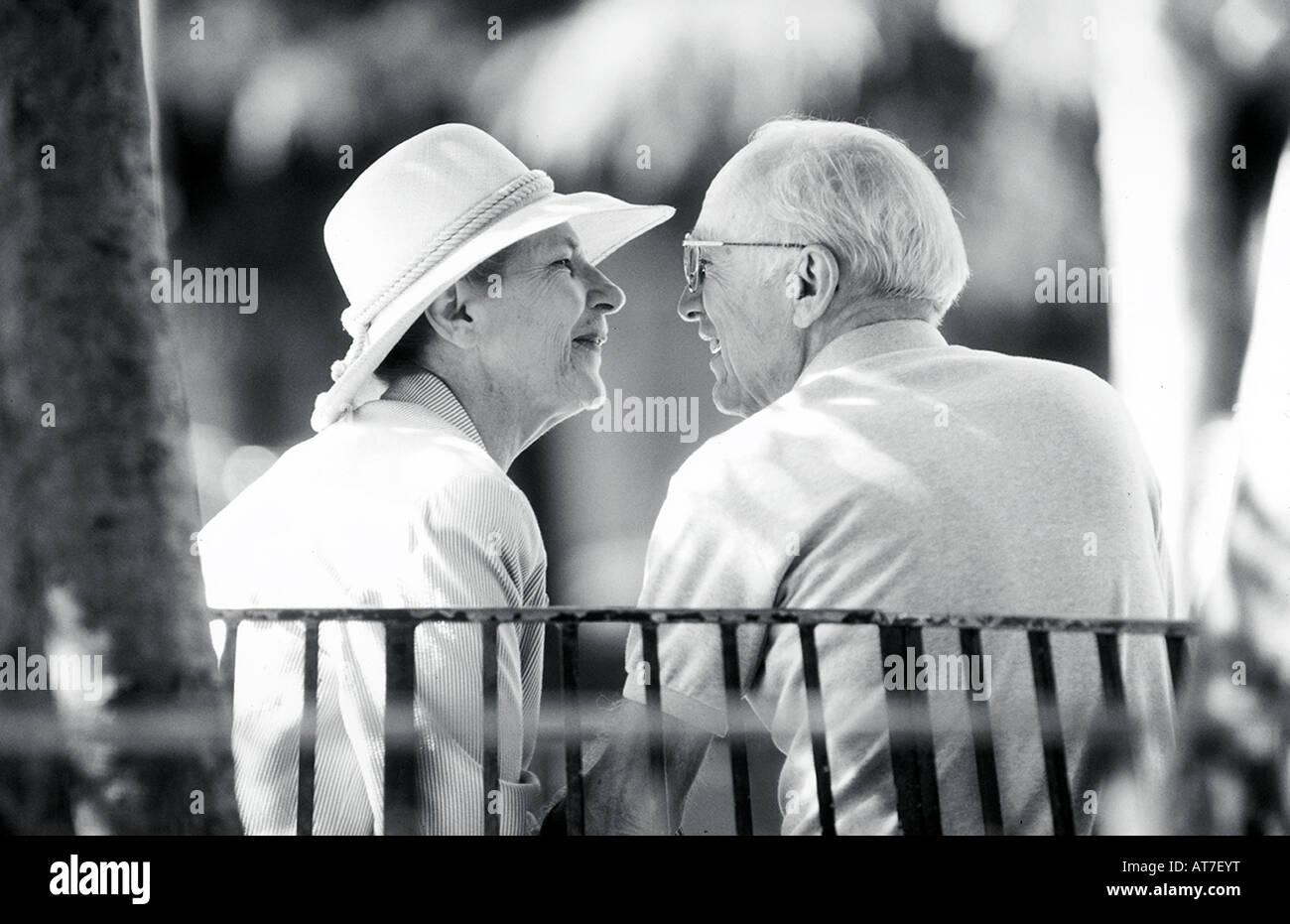 Ein älteres Paar eng auf einer Parkbank im Gespräch Stockbild