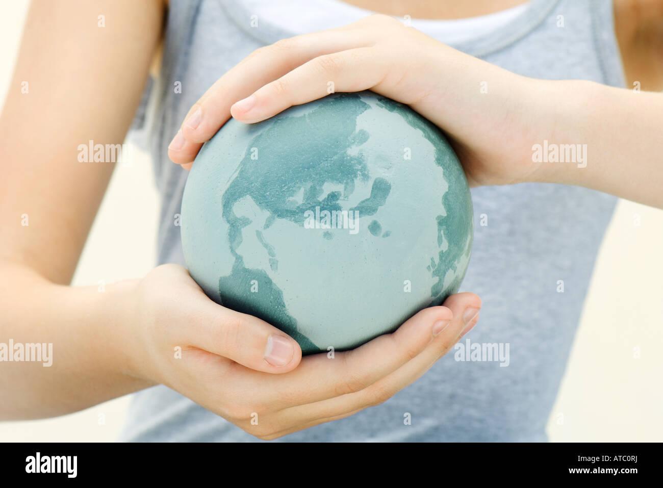 Frau, die Welt in der hohlen Hand, Nahaufnahme, verkürzte Ansicht Stockbild
