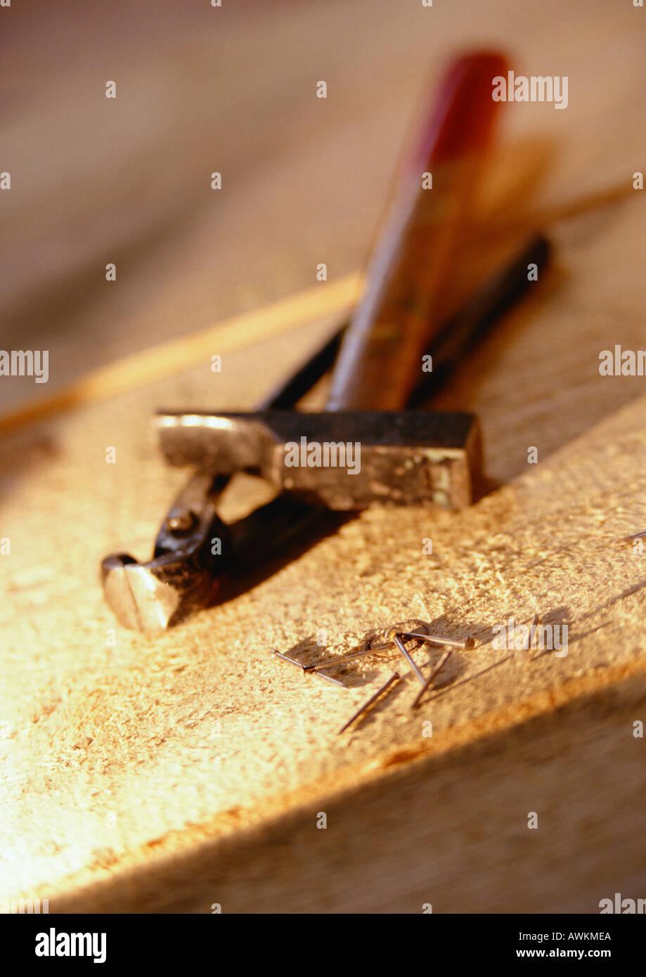 Werkzeuge und Nägel auf Holzbrett Stockbild