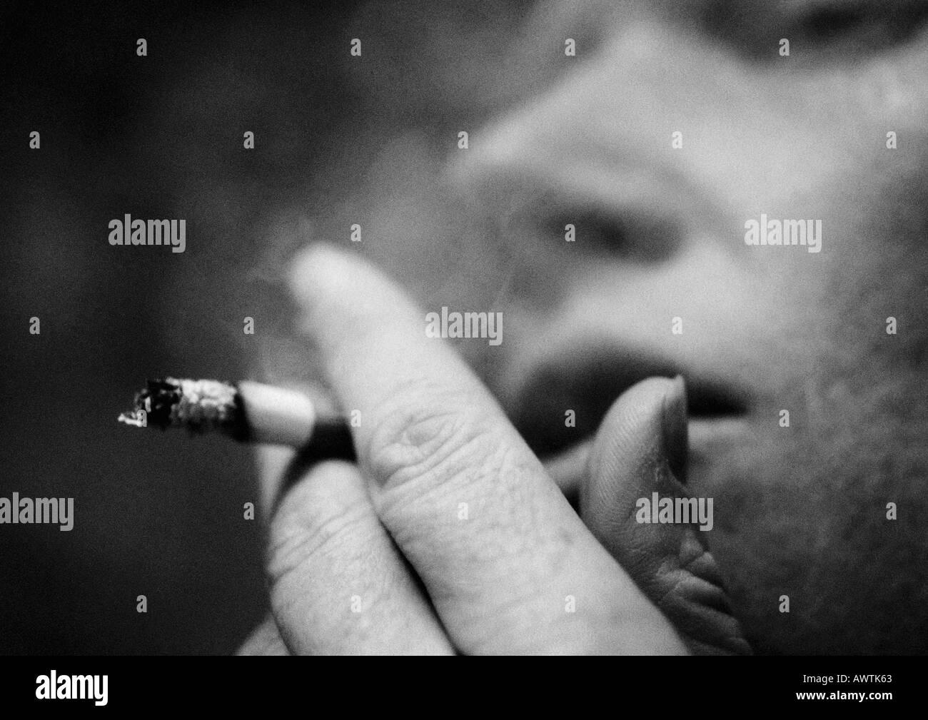 Person qualmender Zigarette, Nahaufnahme, verschwommen, b&w Stockbild