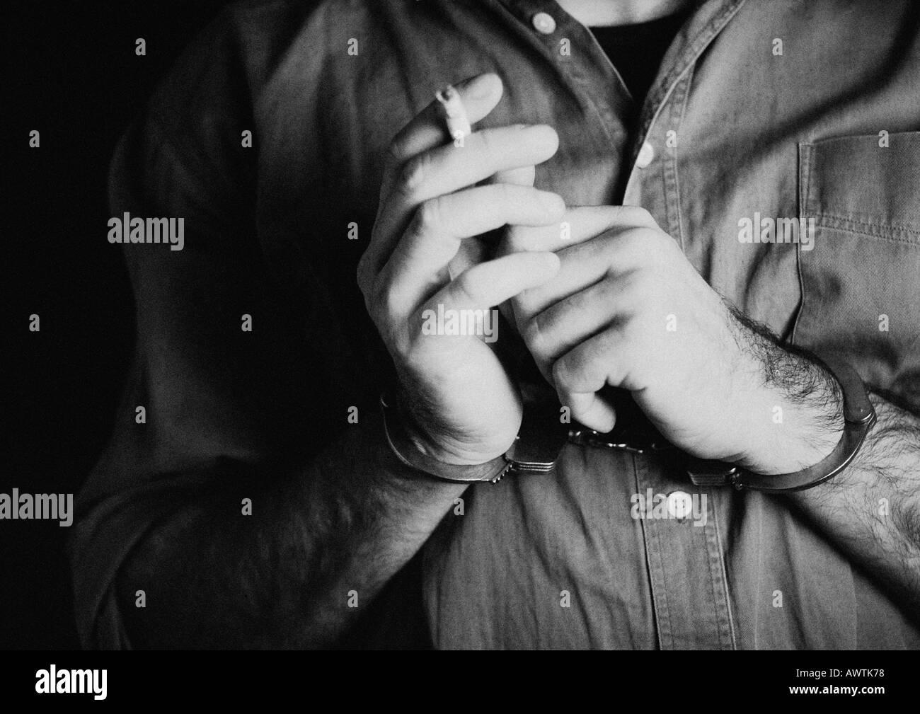 Mann mit Handschellen und Holding Zigarette, Nahaufnahme, b&w Stockbild