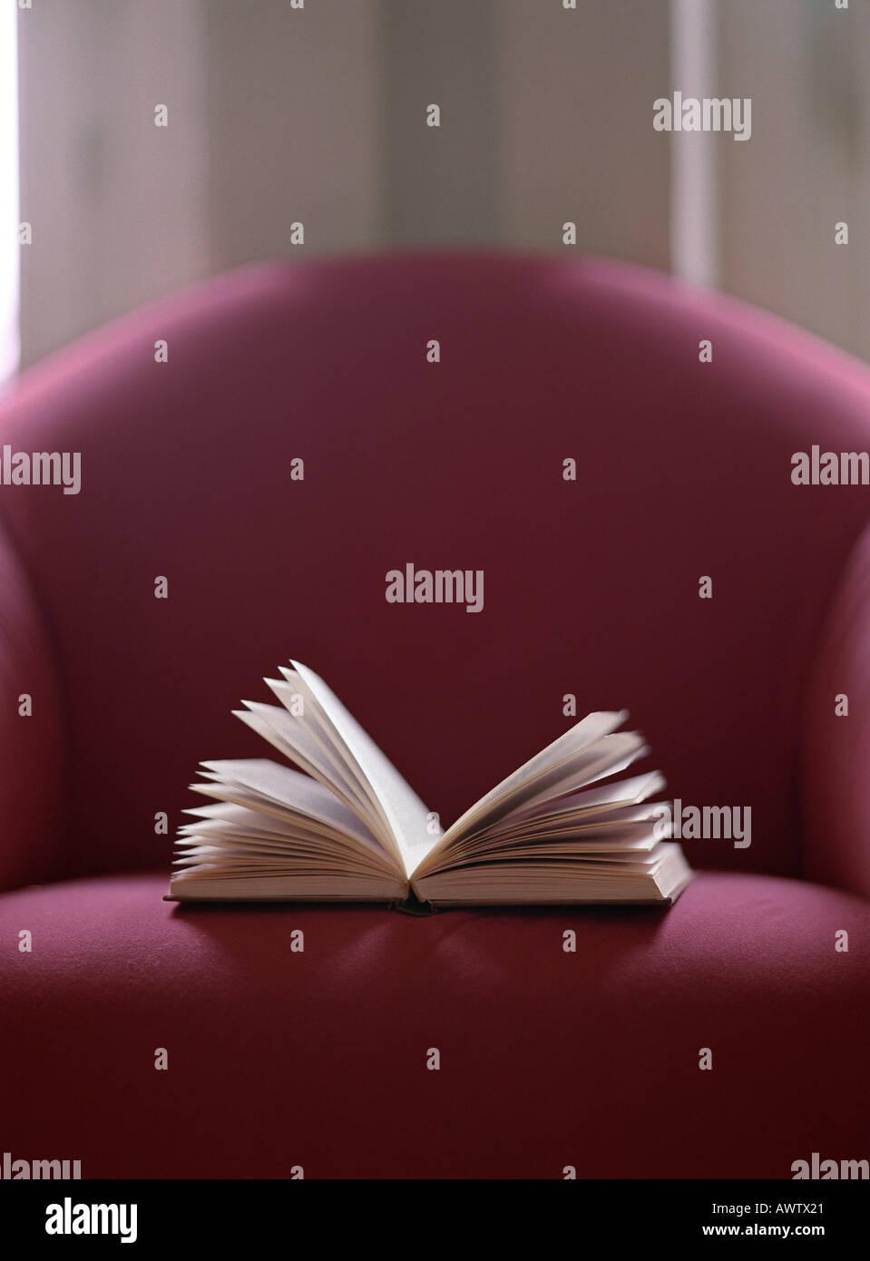 Offenes Buch auf Stuhl. Stockbild
