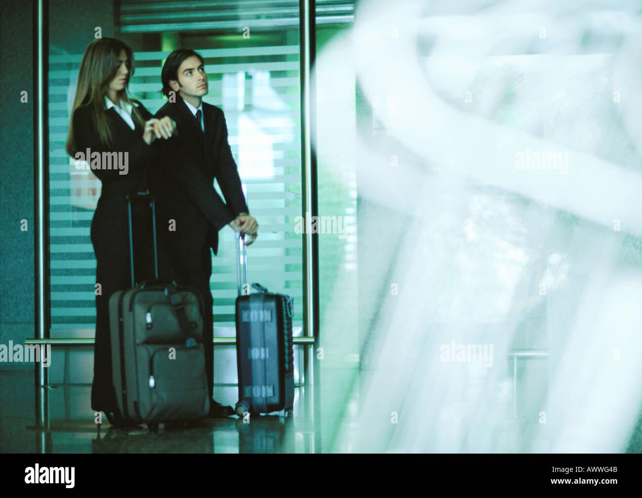 Mann und Frau stehen mit Koffern, Frau betrachten zu sehen. Stockbild