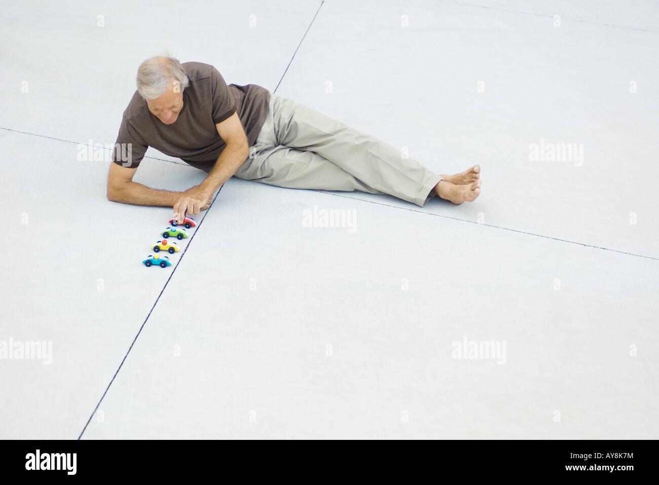 Reifer Mann sitzt auf dem Boden, Schlange, Spielzeugautos, erhöhte Ansicht Stockbild
