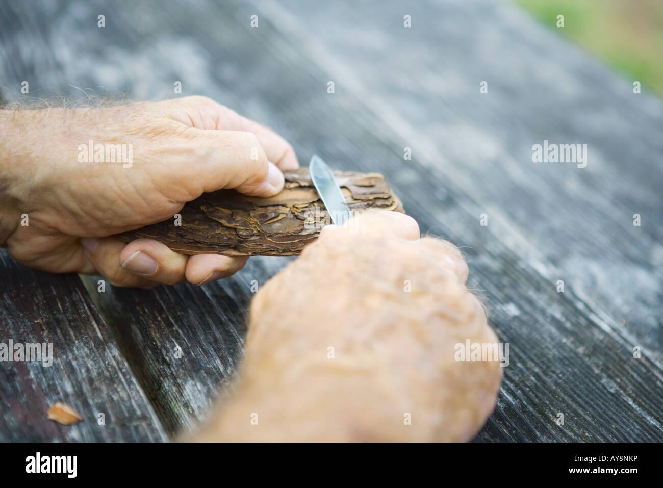 Mann schnitzen Stück Rinde, Blick auf Hände abgeschnitten Stockbild