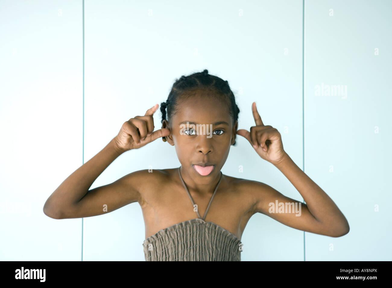 Kleines Mädchen Zunge heraus in die Kamera, erhobenen Armen, Porträt Stockbild