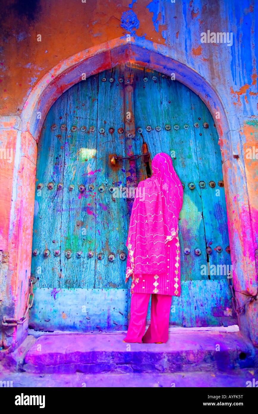 Frau in Old Delhi durch eine bunte Tür, Indien Stockfoto