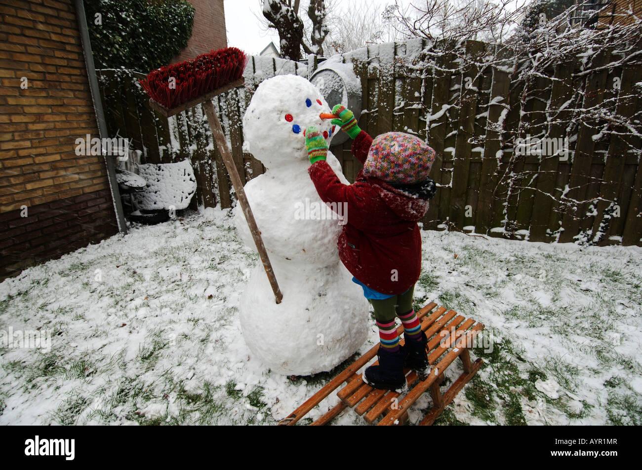 Drei Jahre alten Mädchen, das einen Schneemann in ihrem Garten Stockbild