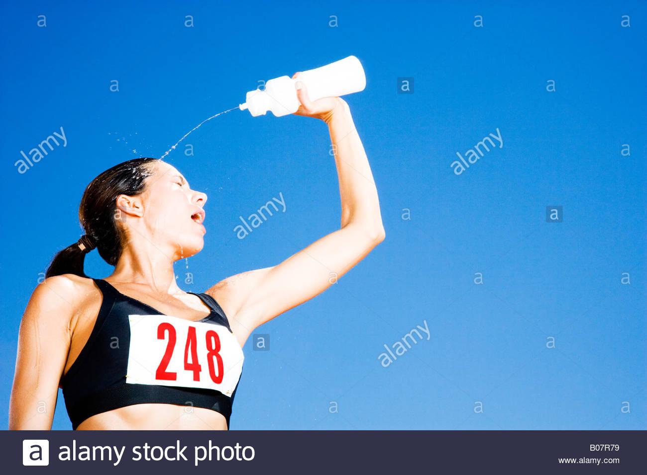 Porträt eines weiblichen Athleten Form eine Flasche Wasser trinken Stockbild