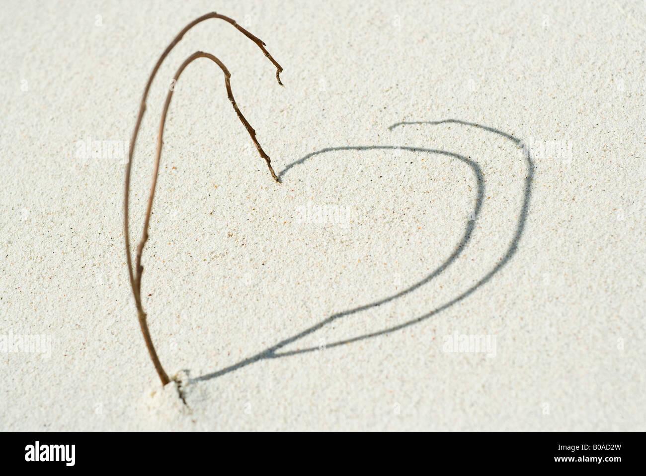 Zweige und Schatten angeordnet in Herzform am Strand, Nahaufnahme Stockbild