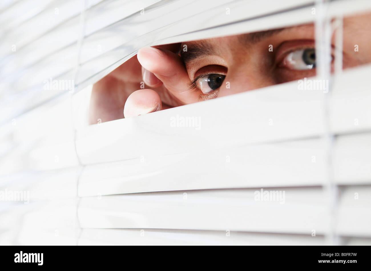 Mann auf der Suche durch Büro Jalousien Stockbild