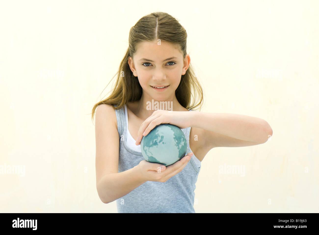 Preteen Mädchen mit kleine Weltkugel in Händen, in die Kamera Lächeln Stockbild