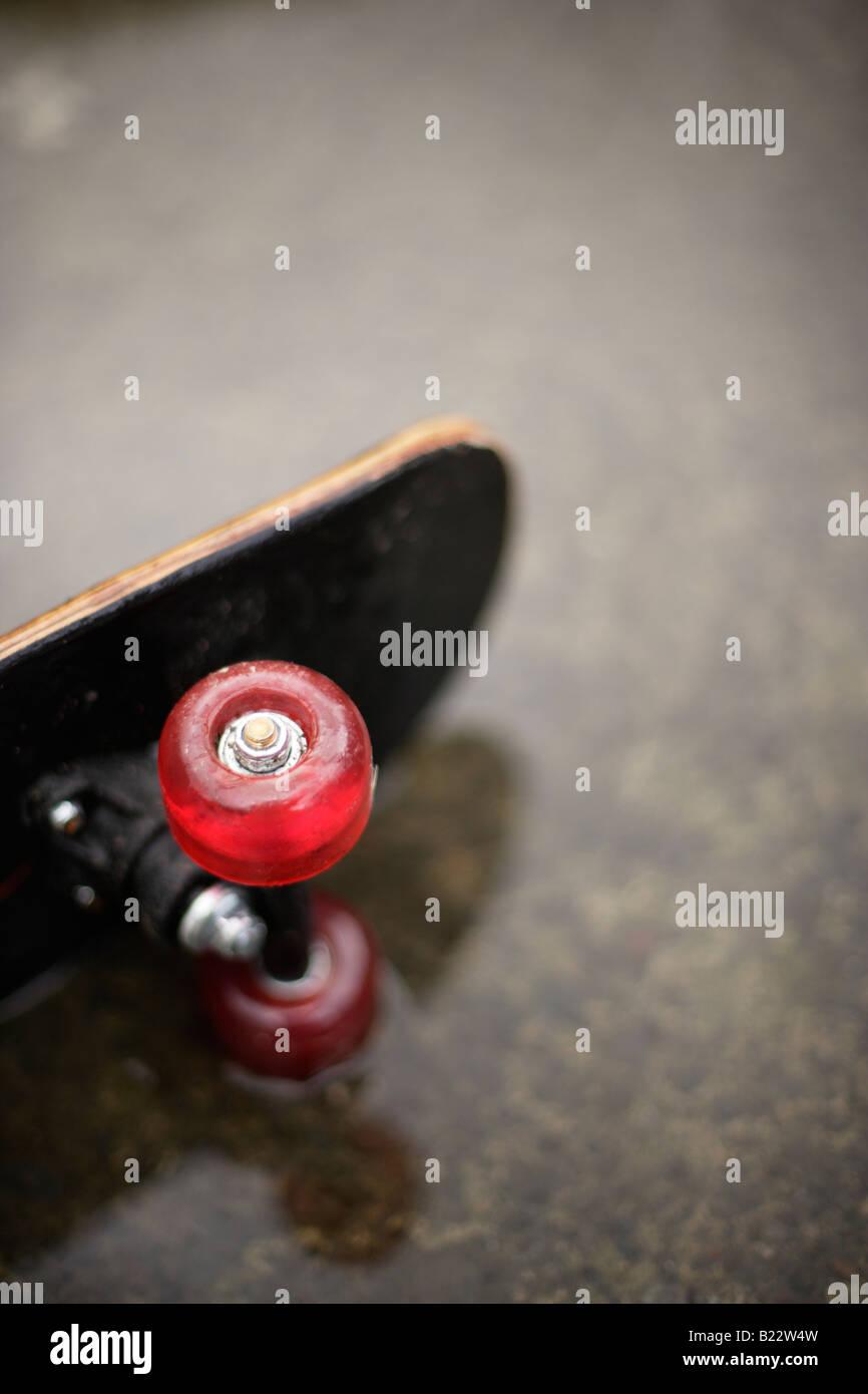 Skateboard in Pfütze Stockfoto
