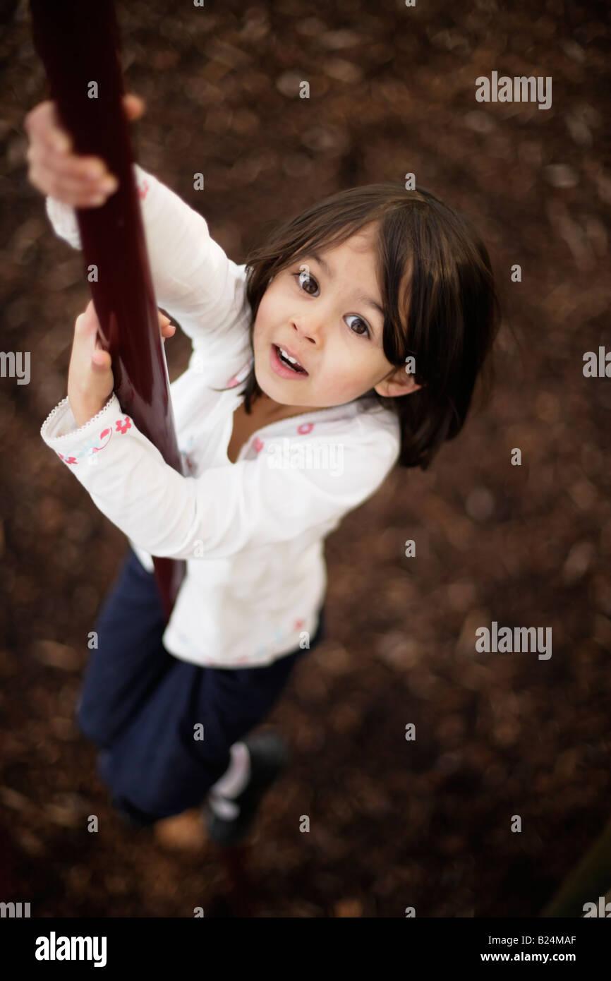 Mädchen im Alter von fünf Stücke in Abenteuerspielplatz Abrutschen Pol Stockbild